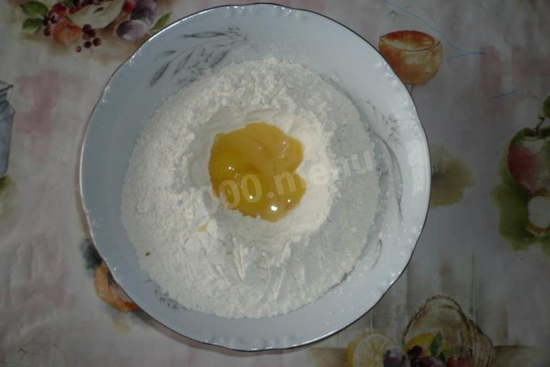 Пшеничную муку высыпаем в миску горкой, делаем в ней углубление, в которое кладем сырые яичные желтки,