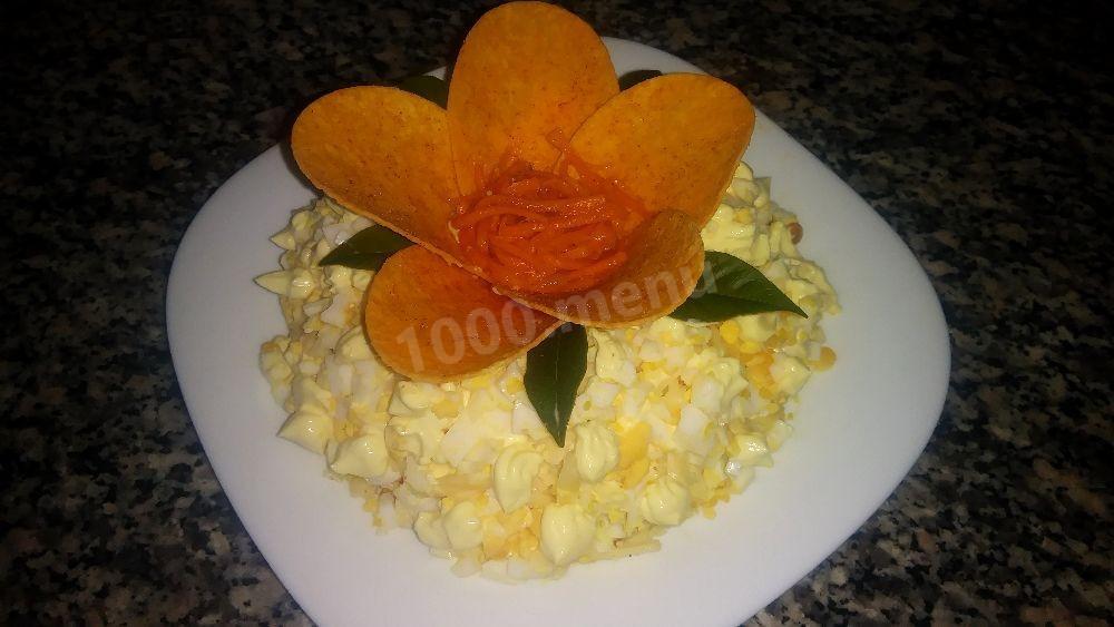 Шаг 5 из чипсов и натертых на мелкой терке желтков сделать цветки и украсить салат.