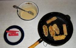 Обмакивать крабовые палочки в кляр и помещать на раскалённую сковороду. Обжаривать с двух сторон до появления корочки.